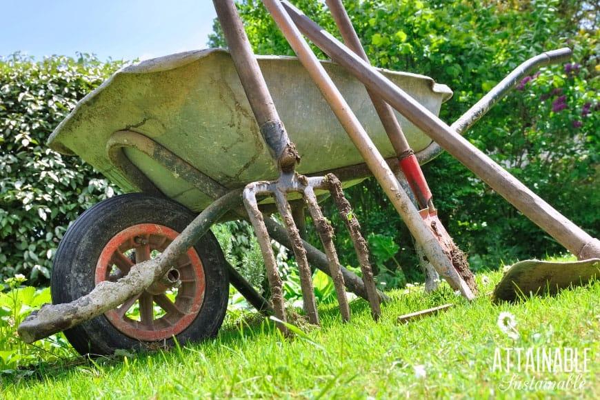 garden tools leaning against a wheelbarrow