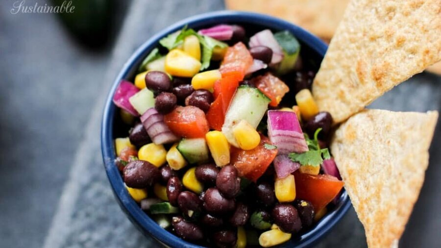 black bean dip with whole beans, corn, and veggies in a blue bowl, with some on a tortilla chip
