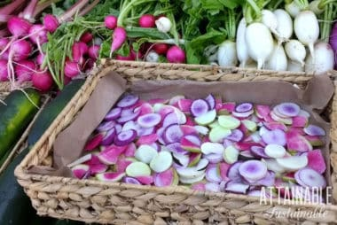 colorful red, pink, and purple radishes in a flat rectangular basket