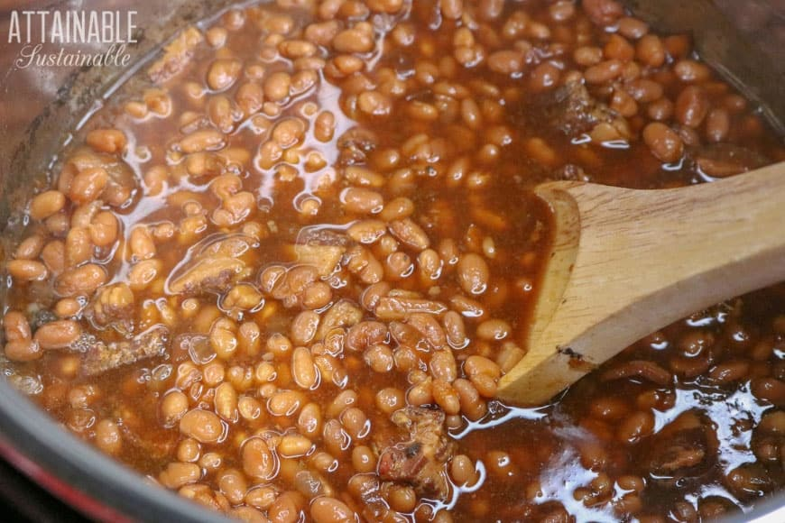 baked beans with a wooden spoon stirring them