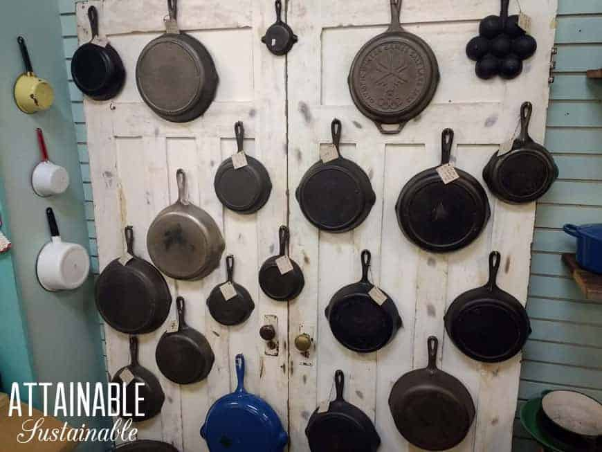 ~20 cast iron skillets hanging on a rustic white wall