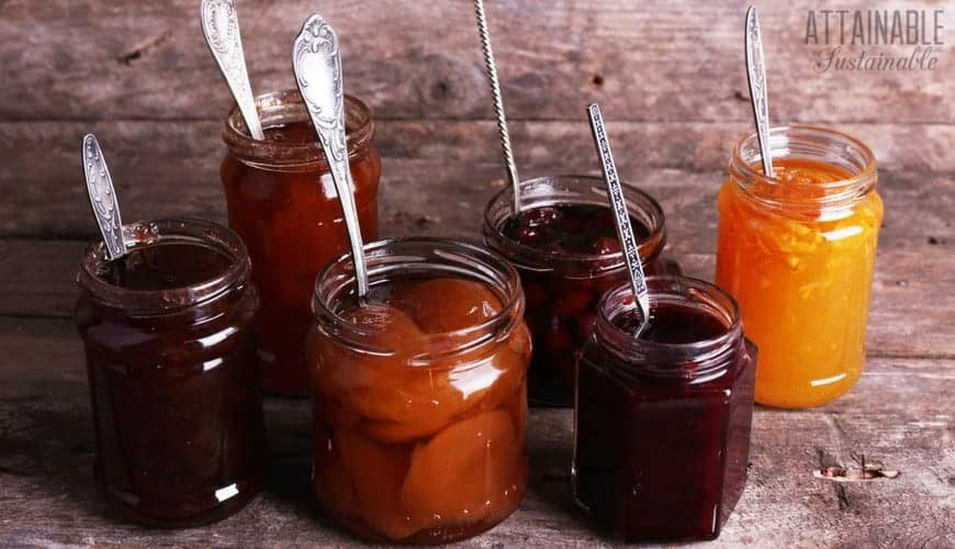 assortment showing difference between jams and jellies in glass jars, each with a metal spoon