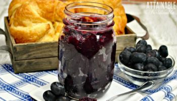 blueberry jam in a canning jar with croissants in the background