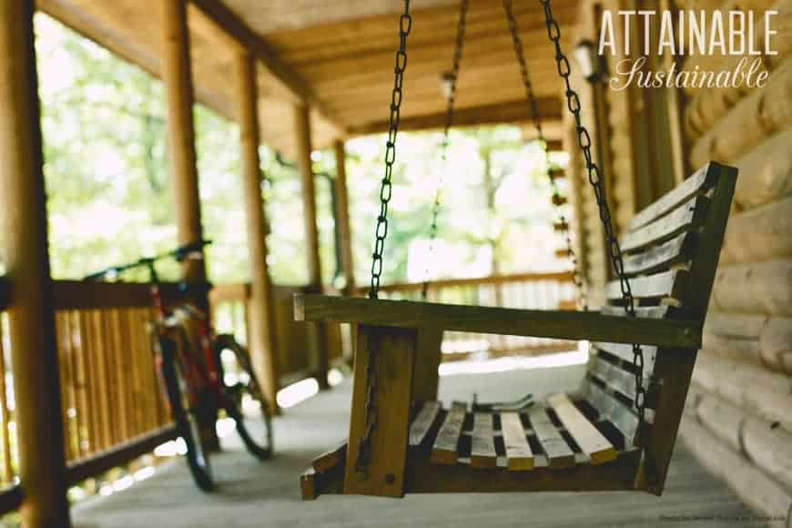 wooden porch swing on a wooden porch with a bicycle in the background