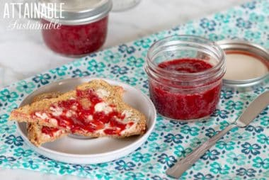 two jars of strawberry compote on a teal napkin with pieces of toast buttered and spread with compote