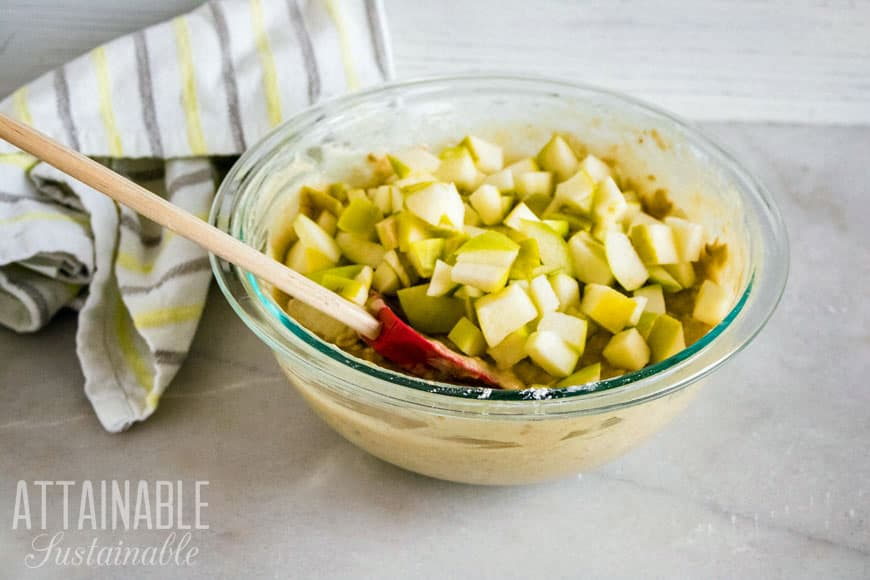 chunks of green apple in a glass bowl: making easy cinnamon apple muffins (white towel with blue stripes in background)