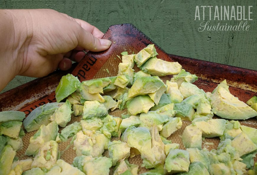 hand lifting chunks of avocados on a silpat, showing how to freeze avocados