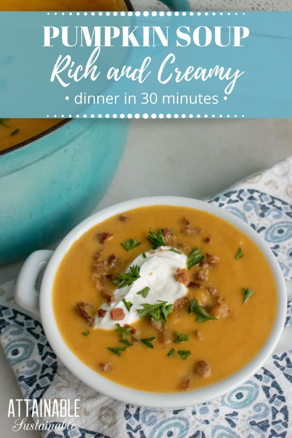 creamy pumpkin soup in white bowl with sour cream and bacon