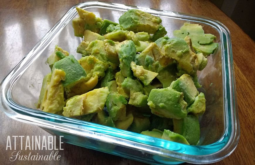 frozen avocados in a glass freezer storage container