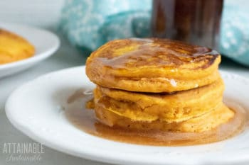 Stack of three easy pumpkin pancakes on a white plate with syrup