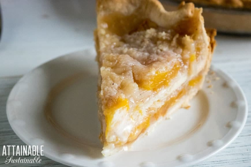 peach pie with crumb topping on a white plate