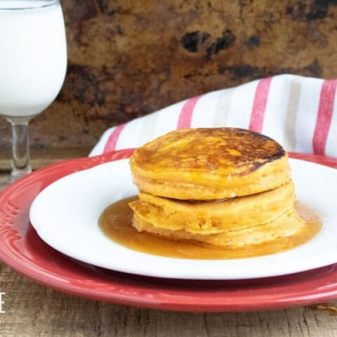 persimmon pancakes on a white dish with a red charger and a glass of milk