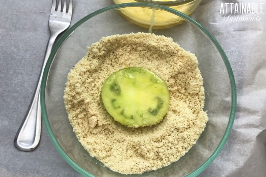 green tomato dipped in egg, sitting in a bowl of almond flour.