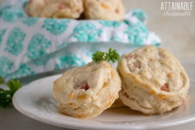 leftover ham and cheese biscuits on a white plate (2) with a basket of biscuits behind