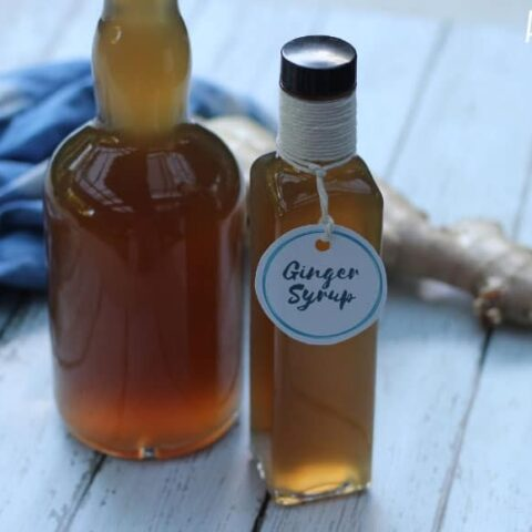 ginger simple syrup in two glass bottles with fresh ginger root