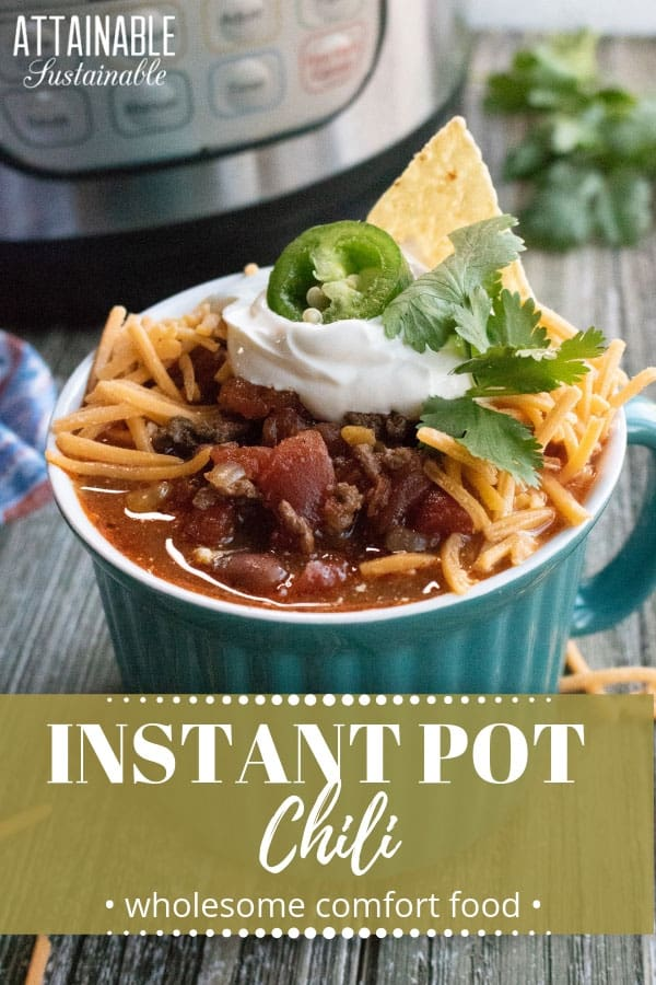 instant pot chili recipe in a teal, ribbed bowl with cheese, sour cream, jalapeno slice, and chip