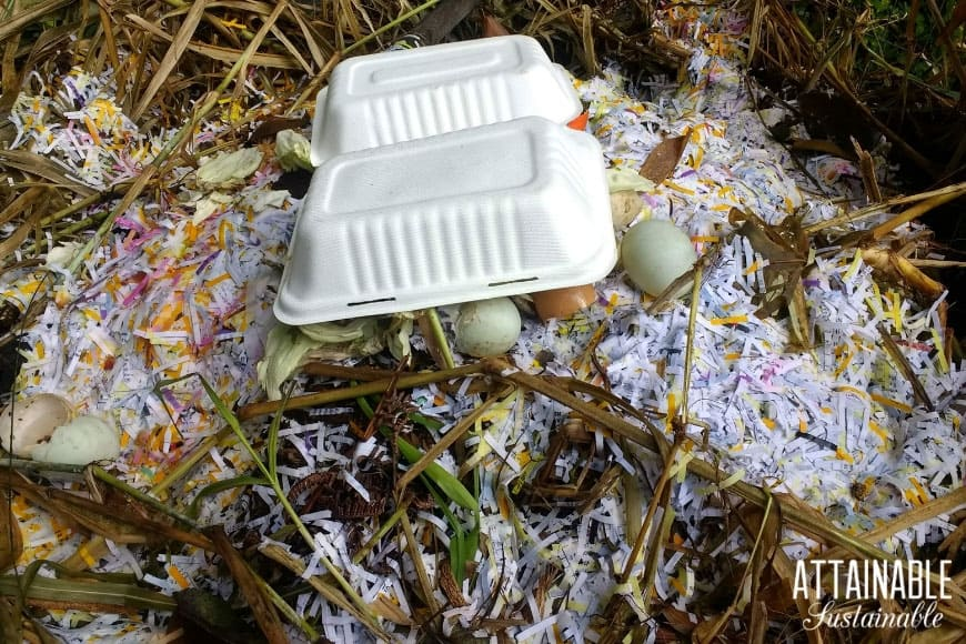 shredded paper and paperboard takeout container in a compost pile
