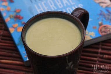 turmeric milk in a mug, with bright blue book behind