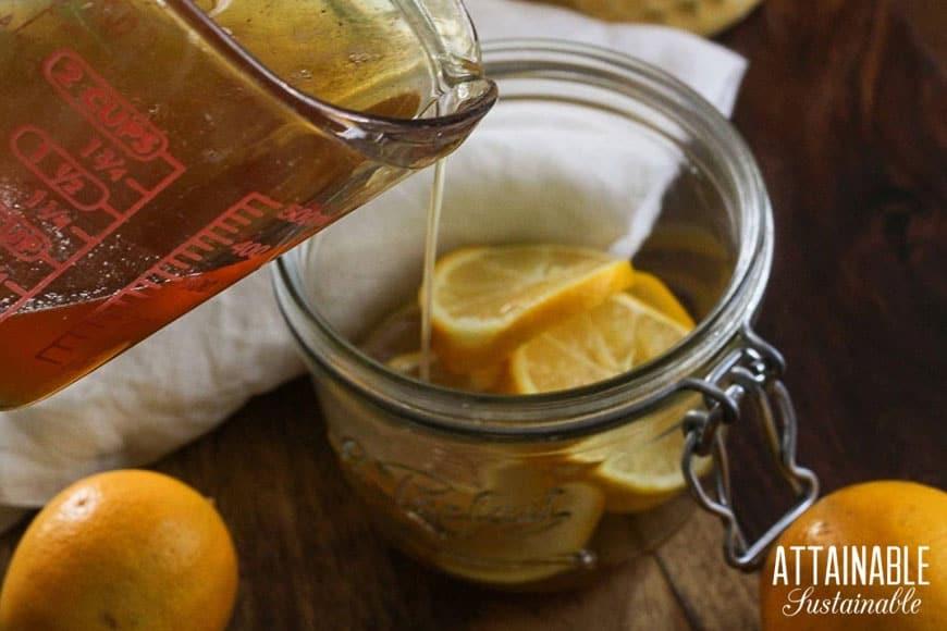 pouring honey into a jar of sliced lemons