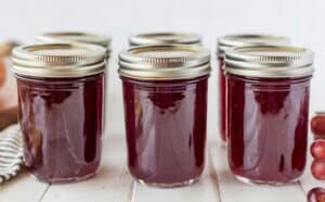 jars of grape jelly with lids in a row