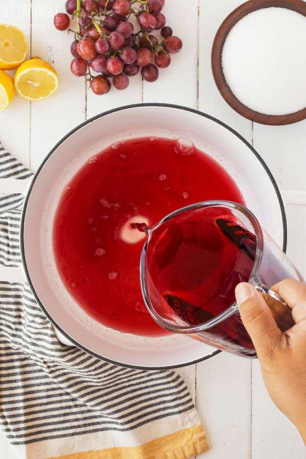 hand pouring grape juice from measuring cup into white porcelain pot