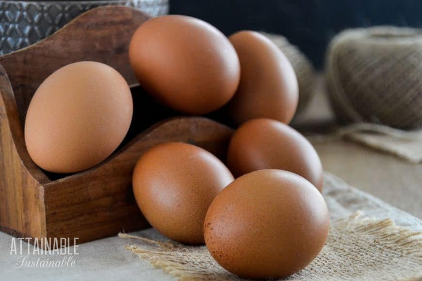 brown eggs stacked in a small wooden box