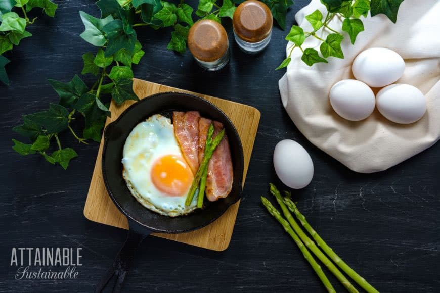 fried farmer's breakfast with canadian bacon and asparagus in a cast iron pan