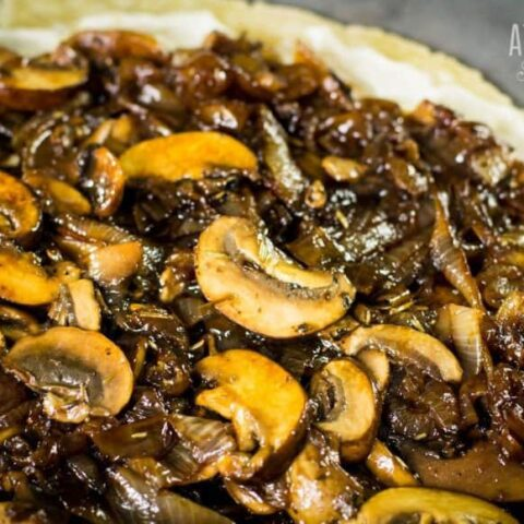 mushrooms and onions spread on a flat pie crust