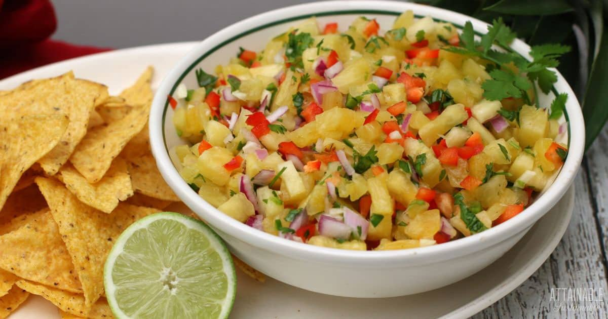 pineapple salsa in a white bowl with chips and a cut lime