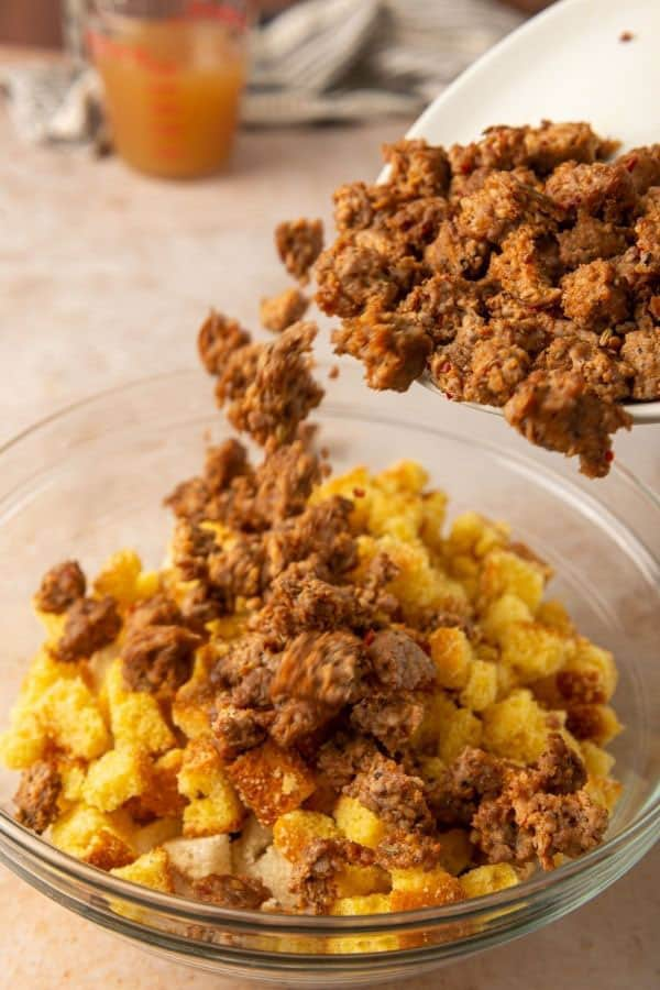 adding cooked sausage to cornbread cubes in a glass bowl