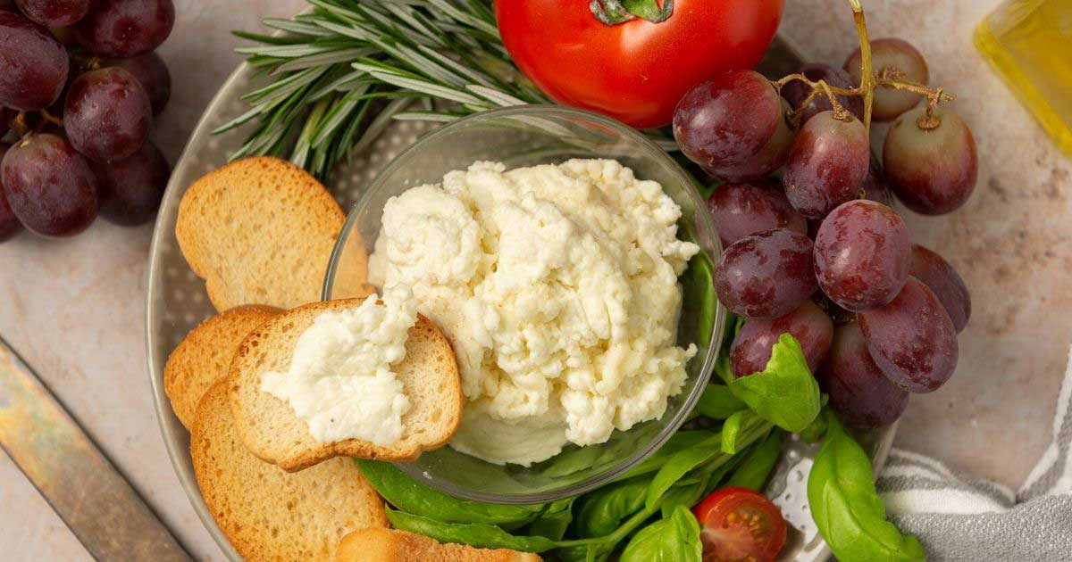 homemade ricotta cheese on a platter with toasted bread and grapes