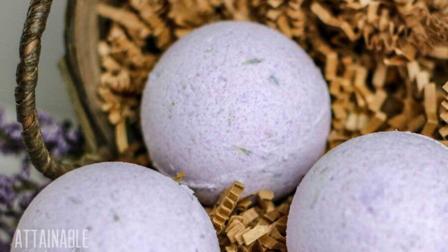 round purple bath bombs in a basket with shredded paper