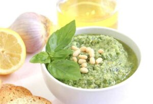 fresh basil pesto in a white dish with basil leaves and pine nuts