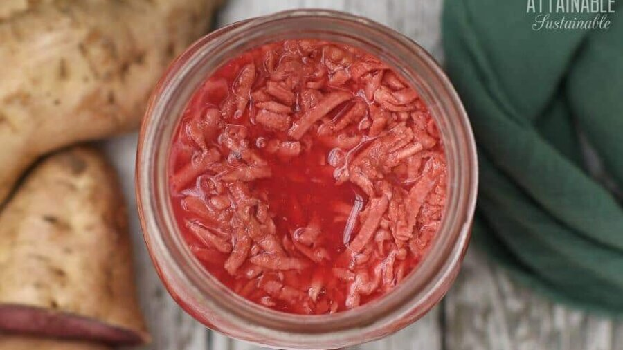 glass jar from above filled with shredded fermented purple sweet potatoes