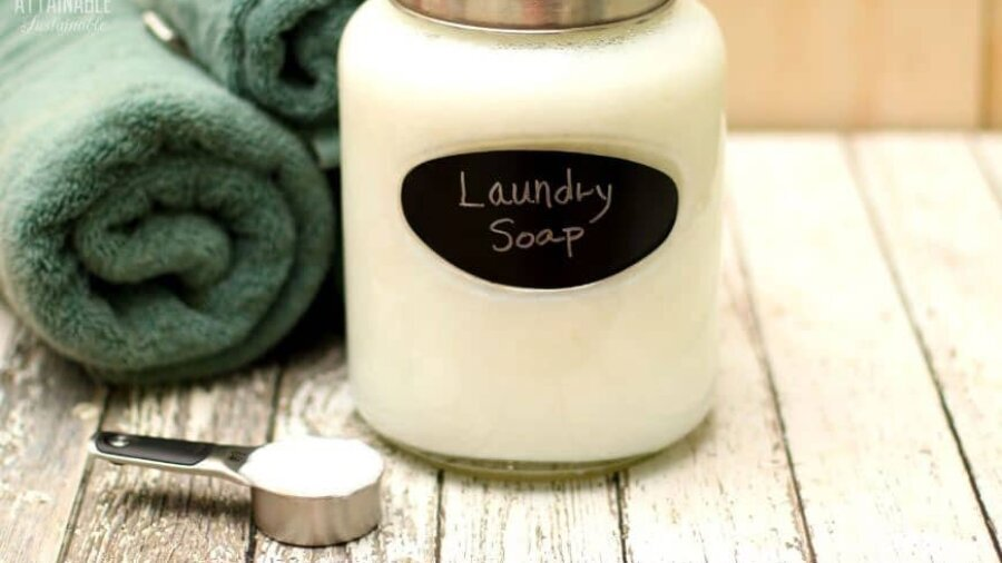 glass jar with white laundry soap and rolled green towels