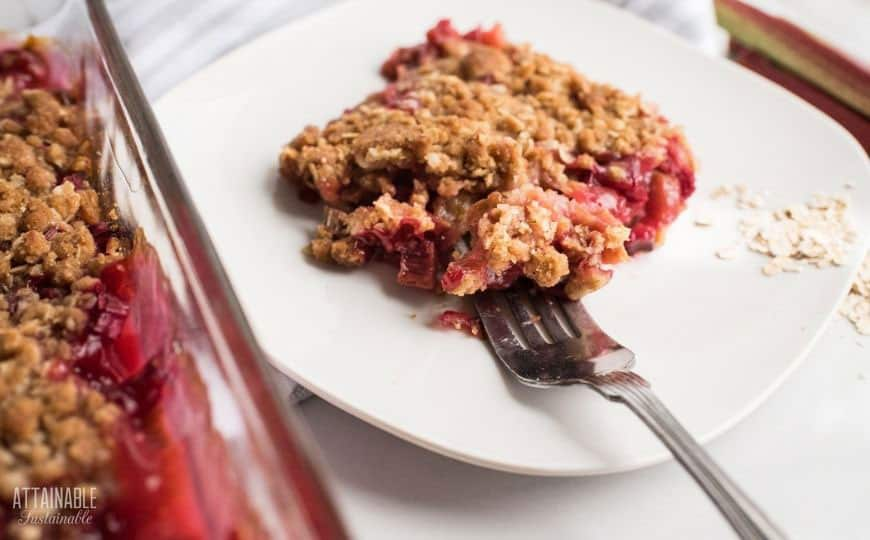rhubarb crisp on a white plate with a fork