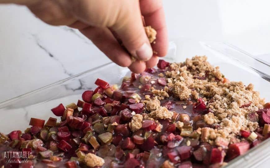 hand adding crumb topping to a rhubarb crisp recipe