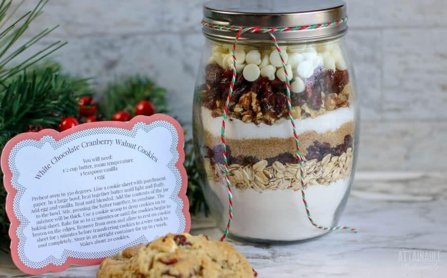 jar of layered ingredients to make cookies, alongside a printed recipe