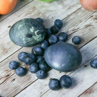 easter eggs dyed dark blue alongside blueberries