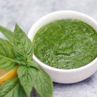 green basil sauce in a white bowl