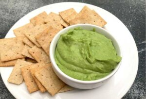 fava bean hummus in a white bowl with crackers