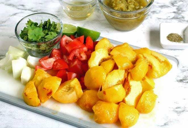 ingredients for fresh peach salsa: quartered peaches, tomato, onion, cilantro on a white tray