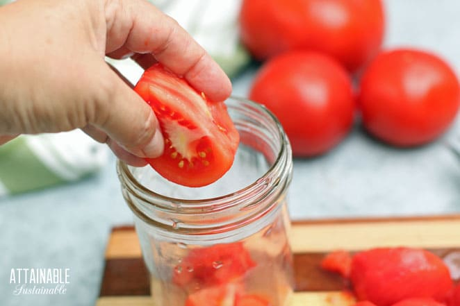 hand dropping a chunk of raw tomato into a jar