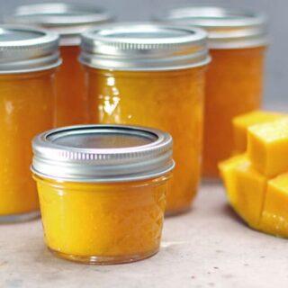 jars of mango jam with a sliced fresh mango