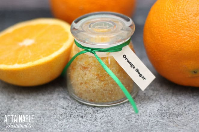 glass jar with orange flavored sugar and a green ribbon