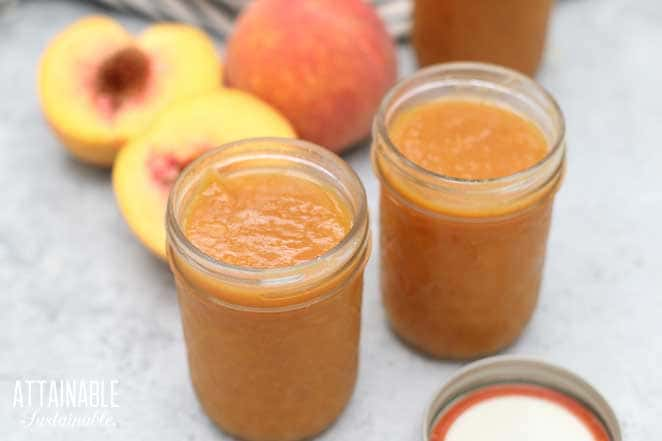 jars of peach butter with lids off, peaches behind